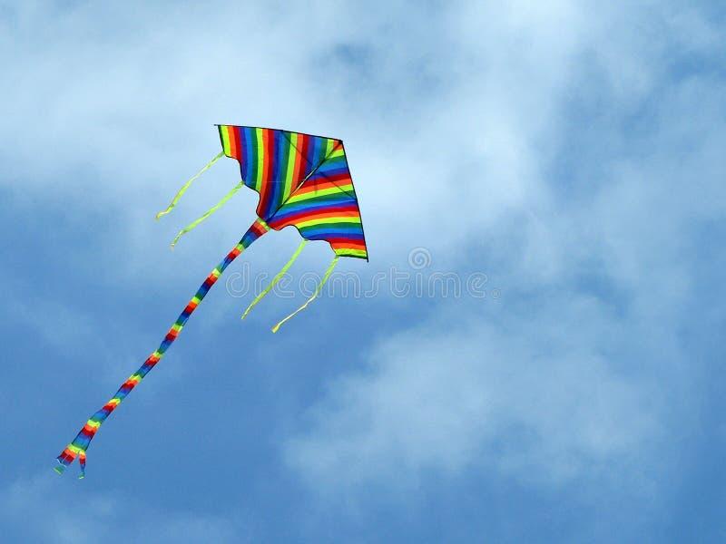 O papagaio de cores iridescentes paira no céu azul Brinquedo da infância alegre Humor sem nuvens Os sonhos voam acima mosca ao cé foto de stock royalty free