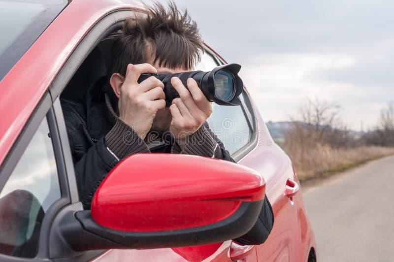 O paparazzi está tomando a foto com a câmera do carro foto de stock royalty free