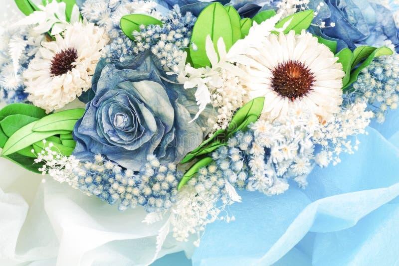 O papel aumentou e secou flores na cor azul e branca, foco macio fotos de stock royalty free