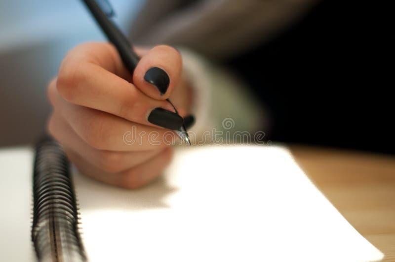 o papel em notas fêmeas da escrita da mão da mulher de negócio em uma tabela enegrece o tratamento de mãos e a letra vazia fotografia de stock royalty free