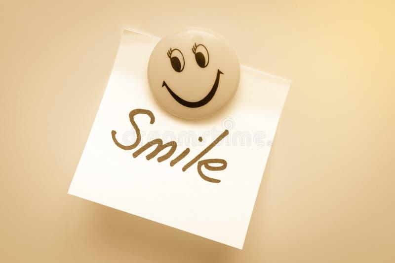 O papel para notas com o sorriso da palavra no ímã é tonificado imagens de stock