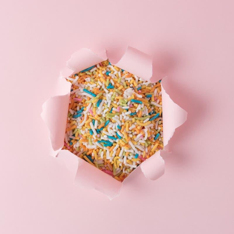O papel rasgado cor-de-rosa vívido com colorido polvilha o fundo Conceito abstrato mínimo imagens de stock royalty free
