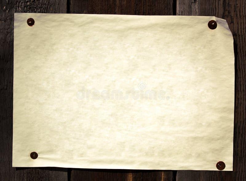 O papel velho tacheou a uma parede de madeira imagens de stock
