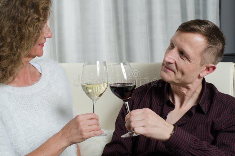 O par é degustação de vinhos no sofá fotografia de stock royalty free