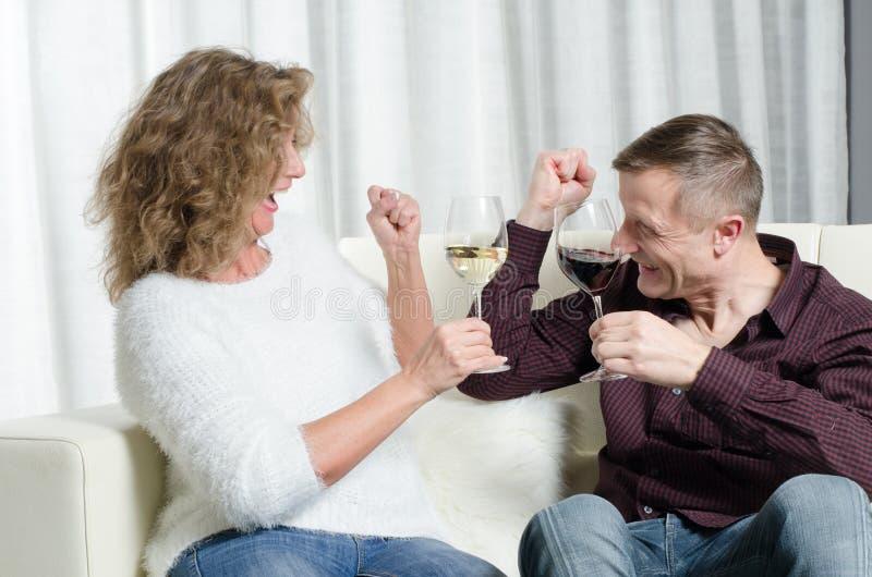 O par é degustação de vinhos no sofá e em cheering fotografia de stock royalty free