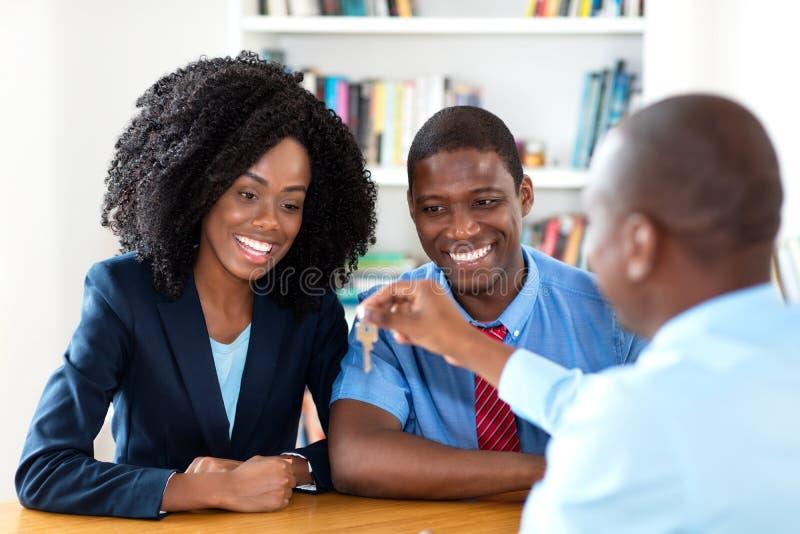 O par afro-americano feliz obt?m a chave para a casa nova foto de stock royalty free