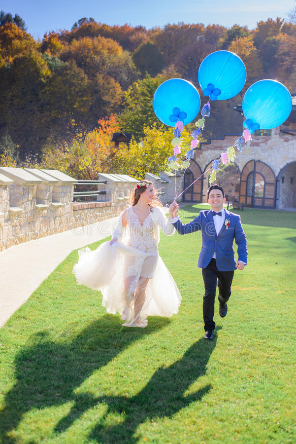 O par alegre do casamento corre ao longo do gramado com balões azuis imagens de stock