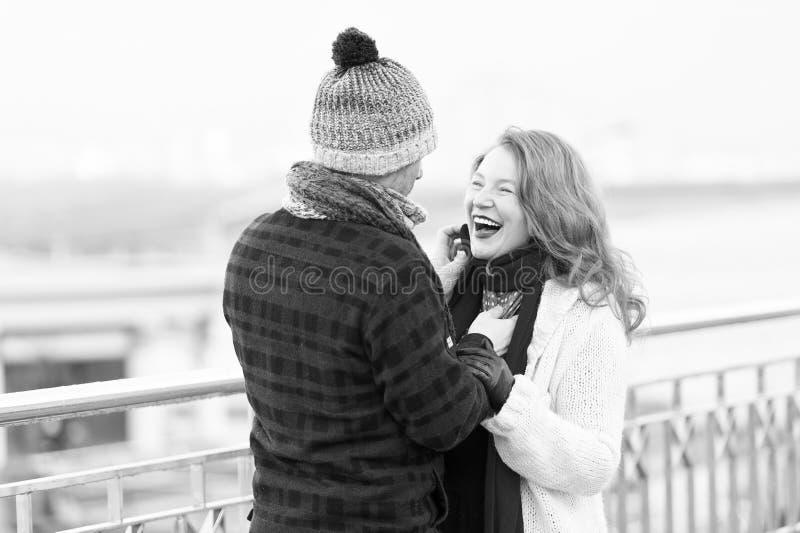 O par ama andar em torno do rio mulher e homem que riem na rua O homem no chapéu de lã faz a mulher engraçada no caspa feito malh foto de stock royalty free