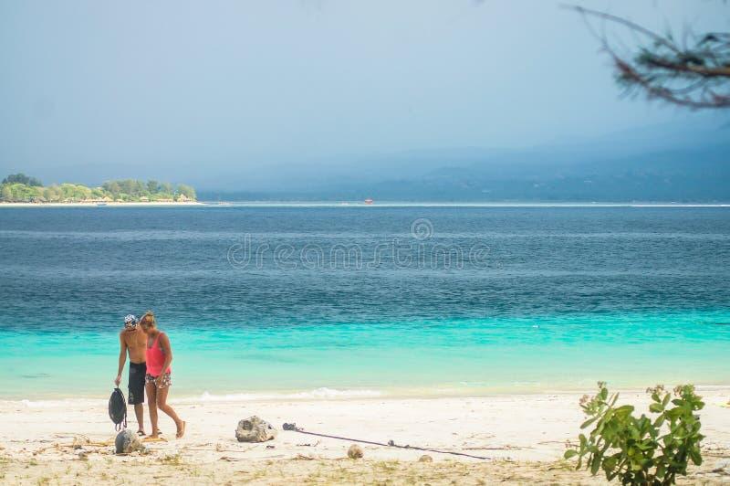 O par anda ao longo do Sandy Beach da ilha tropical de Gili Meno indonésia As montanhas de Lombok no horizonte fotos de stock
