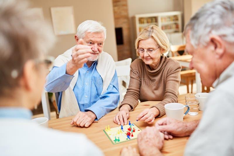 O par aposentado joga com jogo de mesa dos amigos fotografia de stock royalty free