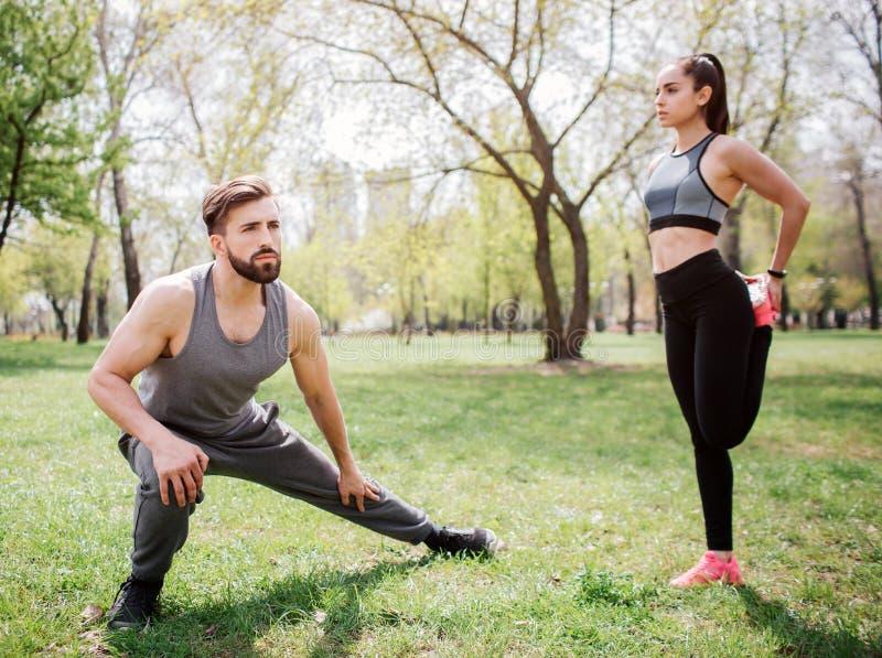 O par bonito está esticando fora no parque O indivíduo é squating e de esticão seus pés quando sua amiga estiver fotos de stock royalty free