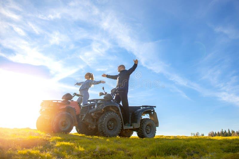 O par bonito está olhando o por do sol da montanha que senta-se no quadbike do atv imagens de stock royalty free