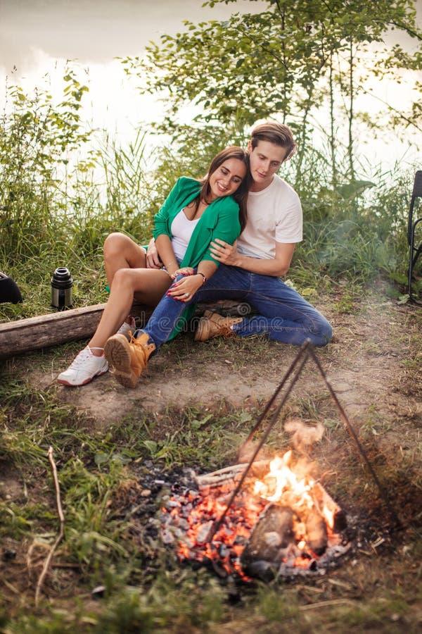 O par bonito está sentando-se perto da fogueira no banco do rio imagem de stock