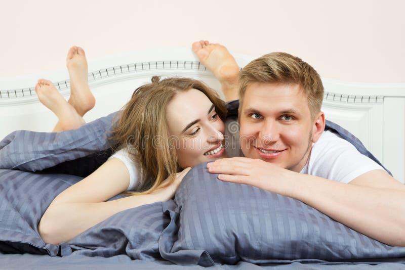 O par de amor bonito est? encontrando-se na cama no quarto na manh? Pares felizes novos que encontram-se na cama e no sorriso foto de stock