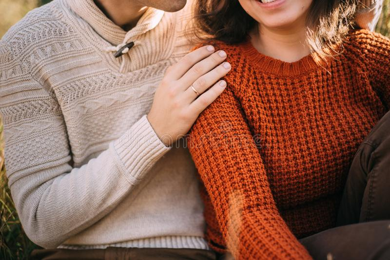 O par de amor está abraçando o assento na grama imagem de stock