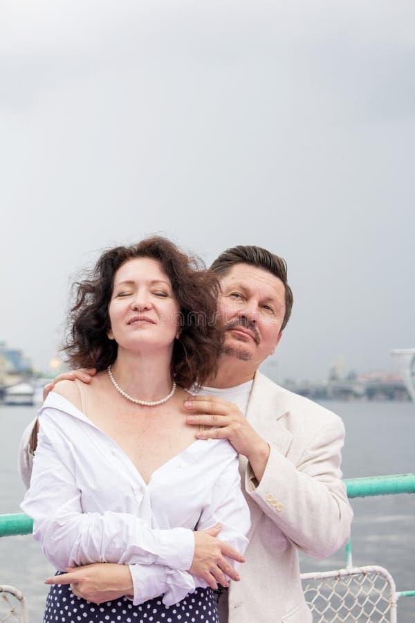 O par de meia idade abraça o amor verdadeiro sensual da emoção dos sentimentos fotografia de stock royalty free
