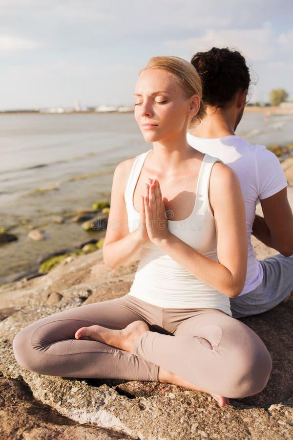 O par de sorriso que faz a ioga exercita fora fotografia de stock