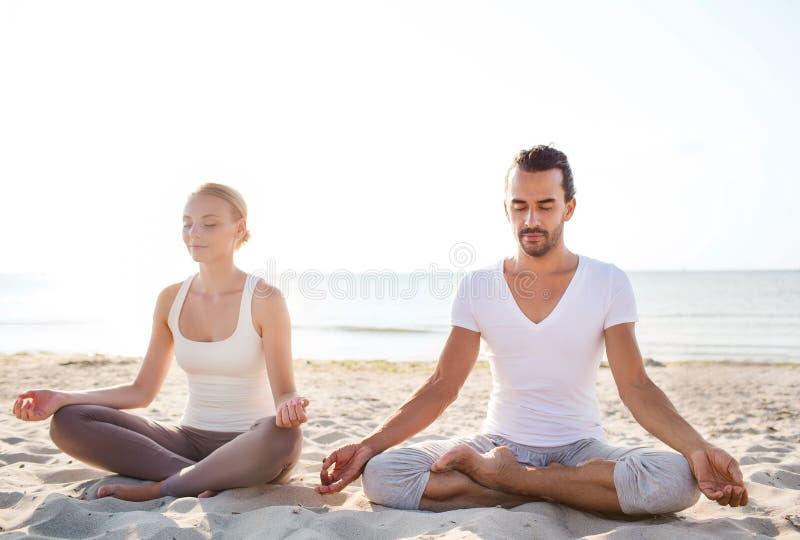 O par de sorriso que faz a ioga exercita fora imagem de stock
