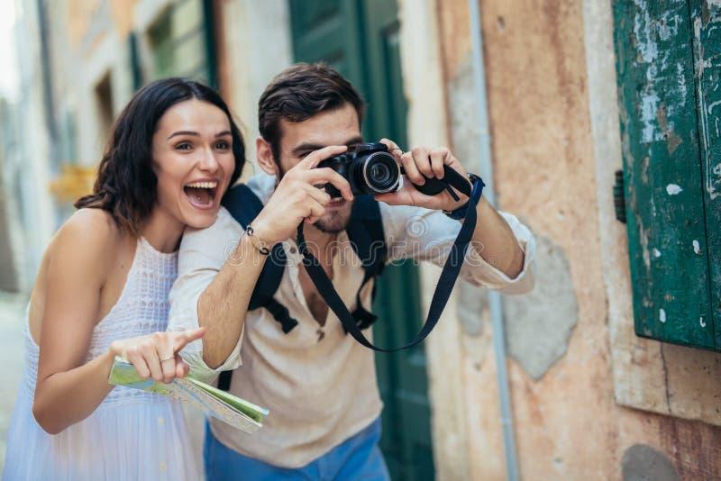 O par de turistas está explorando a cidade nova junto imagens de stock royalty free