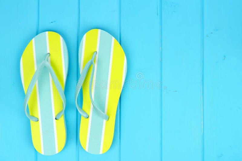 O par de verão brilhante flip-flops contra a madeira azul fotografia de stock