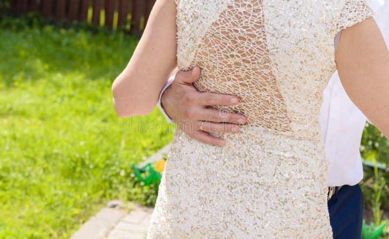 O par do casamento guarda as mãos ao dançar A mão do noivo na parte traseira da noiva fotografia de stock
