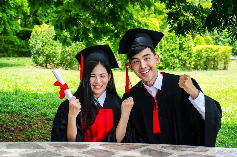 O par do homem e da mulher vestido no vestido ou em graduados pretos da graduação com felicitações com diploma da posse à disposi fotos de stock royalty free