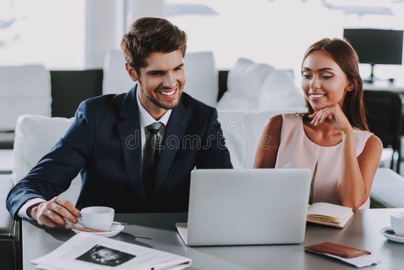 O par elegante de sorriso está usando o portátil no café fotografia de stock