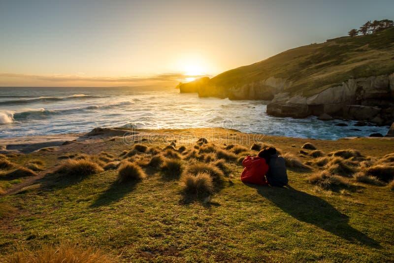 O par está apreciando o por do sol bonito na praia do túnel de Nova Zelândia imagens de stock