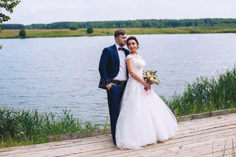 O par está em uma ponte de madeira no banco de rio imagem de stock