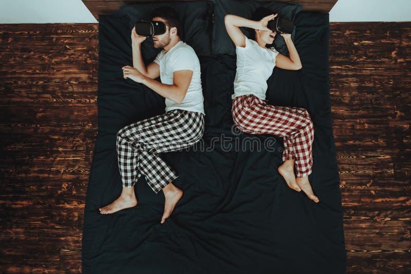 O par está usando vidros da realidade virtual na cama imagens de stock