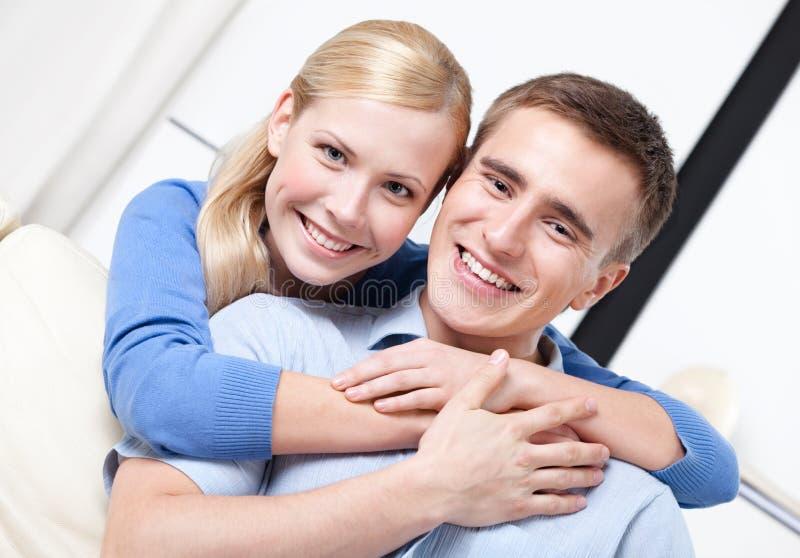 O par feliz abraça-se no sofá fotos de stock royalty free