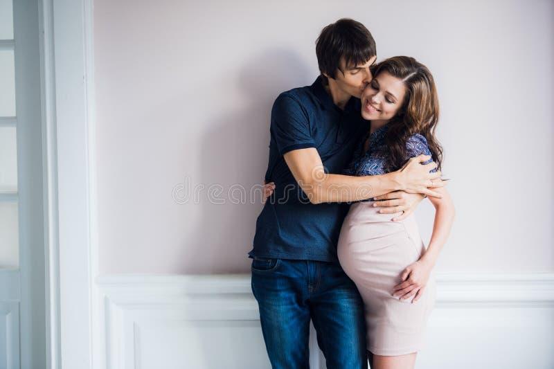 O par feliz de sorriso que espera uma criança inclina-se entre si em casa fotos de stock royalty free