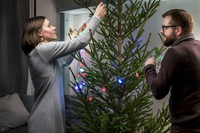O par feliz decora uma árvore de Natal com festão colorido Preparação por o ano novo imagens de stock royalty free