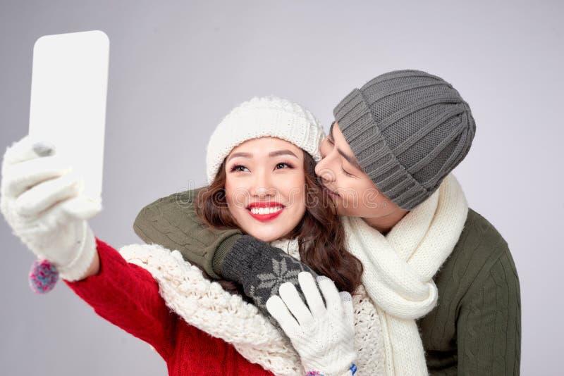 O par feliz em seu inverno veste a tomada da imagem com smartphone imagens de stock