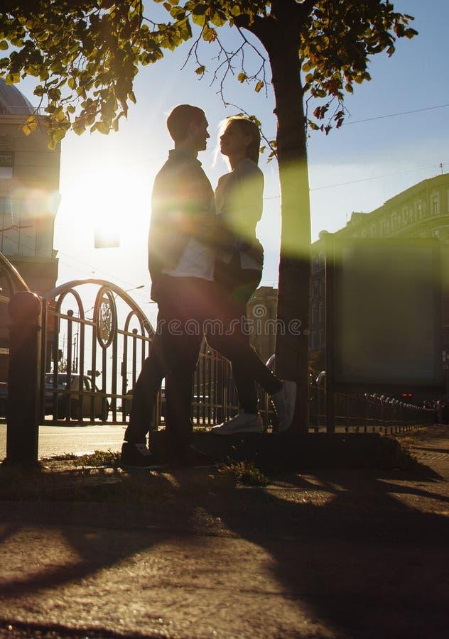 O par feliz está abraçando na rua, os raios dos sóis para brilhar em suas caras, fundo escuro Data na cidade imagem de stock royalty free
