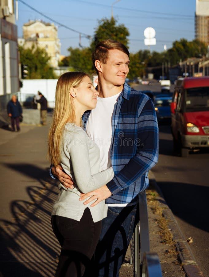 O par feliz está abraçando na rua, perto da estrada suporte perto da cerca ao lado do caminho fotografia de stock