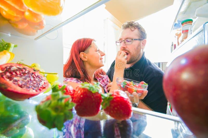 O par feliz está comendo a morango do refrigerador imagem de stock royalty free