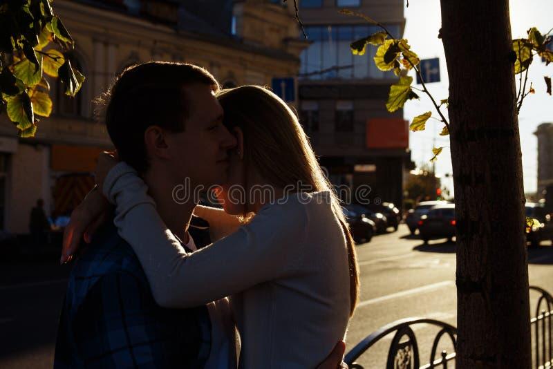 O par feliz est? abra?ando na rua, os raios dos s?is para brilhar em suas caras, fundo escuro Data na cidade imagens de stock royalty free