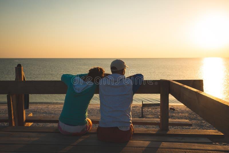 O par feliz relaxa em uma varanda do bungalow imagem de stock