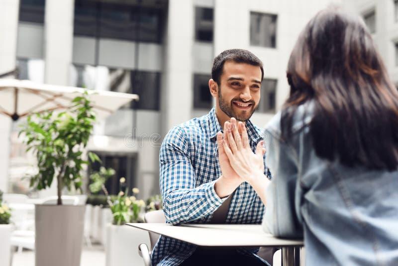 O par feliz toca em suas mãos ao sentar-se na tabela no café fotos de stock