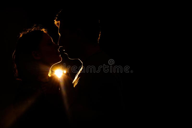 O par loving que estão na obscuridade, e sua silhueta iluminam os raios foto de stock royalty free