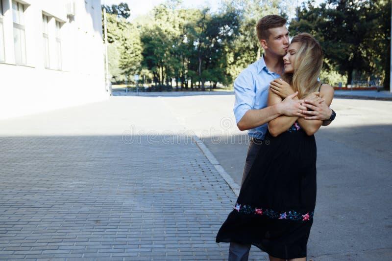 O par no amor abraça contra o contexto de uma construção na cidade, sorrir, atraído data, o dia de Valentim do amor fotos de stock royalty free