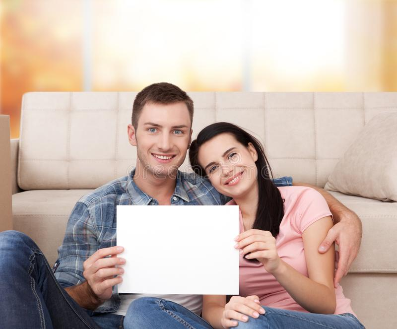 O par novo bonito é de sorriso e mostrando o papel vazio ao sentar-se no assoalho no apartamento novo imagens de stock