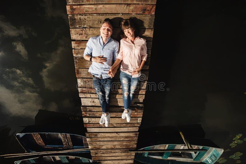 O par novo bonito encontra-se em uma ponte de madeira no lago, olha-se lovingly em se e em sorrisos Hist?ria de amor fotografia de stock