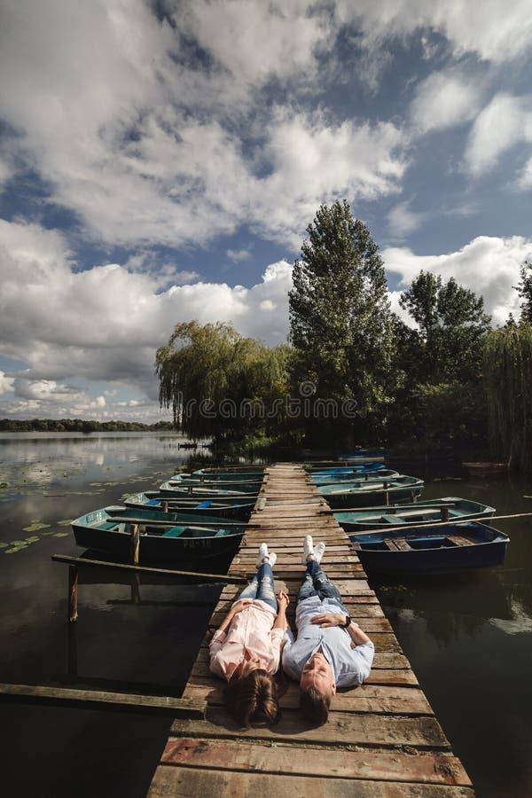 O par novo bonito encontra-se em uma ponte de madeira no lago, olha-se lovingly em se e em sorrisos Hist?ria de amor fotos de stock