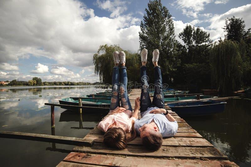 O par novo bonito encontra-se em uma ponte de madeira no lago, olha-se lovingly em se e em sorrisos Hist?ria de amor fotos de stock royalty free