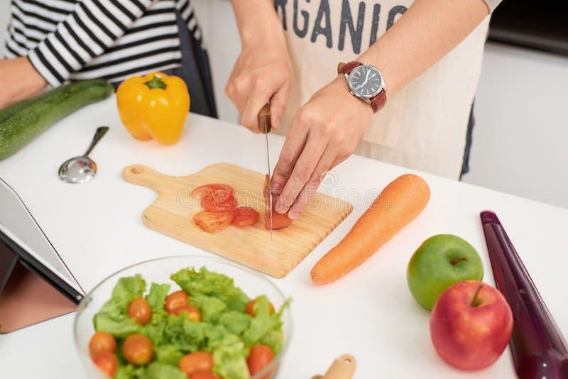 O par novo bonito está cozinhando na cozinha em casa O homem está cozinhando com Moman está usando uma tabuleta e um sorriso digi foto de stock royalty free