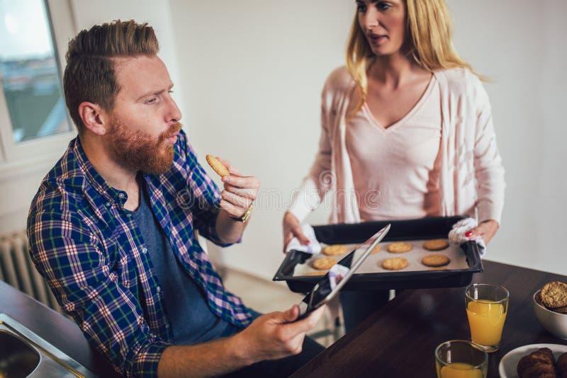 O par novo bonito está usando uma tabuleta digital e está sorrindo ao cozinhar na cozinha imagem de stock