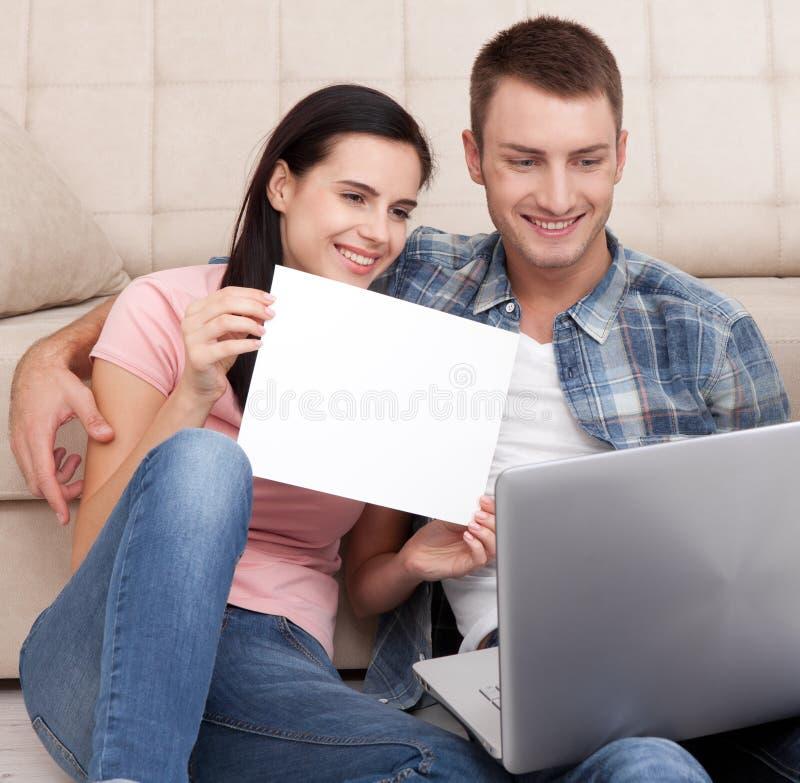 O par novo bonito que usa o portátil comunica-se no bate-papo video Uma mulher é de sorriso e mostrando o pedaço de papel vazio foto de stock