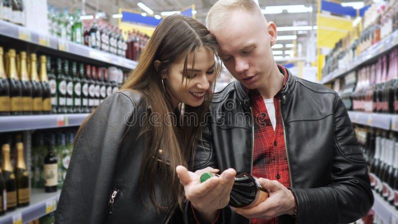 O par novo compra produtos em um supermercado, escolhe uma garrafa da etiqueta da leitura do vinho imagens de stock